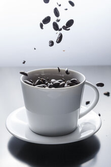 Coffee beans falling in a white coffee cup - BZF000134