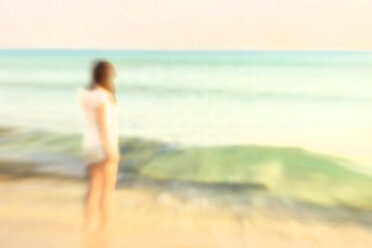 Spain, Baleares, young woman standing at seafront - CMF000245