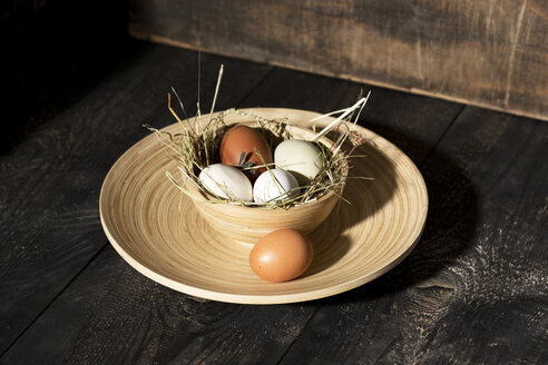 Easter nest with eggs in bowl on dark wood - MAEF010245