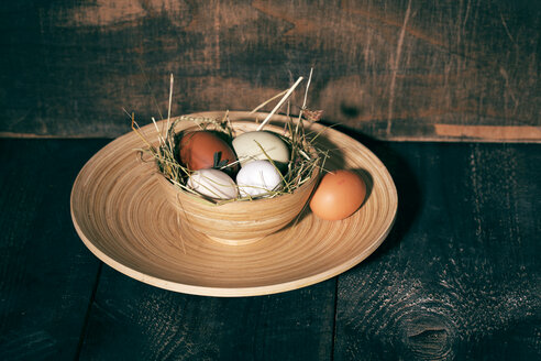 Easter nest with eggs in bowl on dark wood - MAEF010246