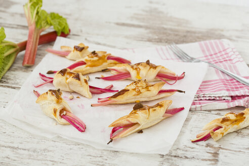 Rhubarb in puff pastry with almond slivers on paper and kitchen towel - MAEF010277