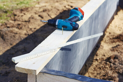 Screw, cordless drill driver and a folding ruler on the corner of a raised bed - HAW000778