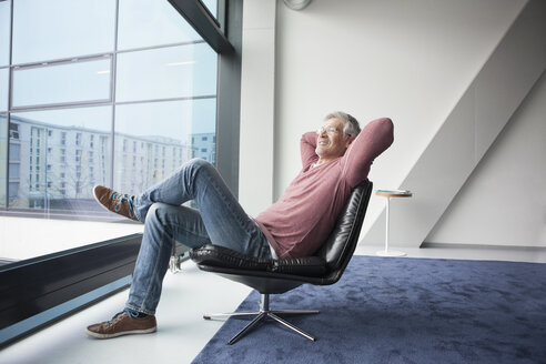Man relaxing in a leather chair at home - RBF002612