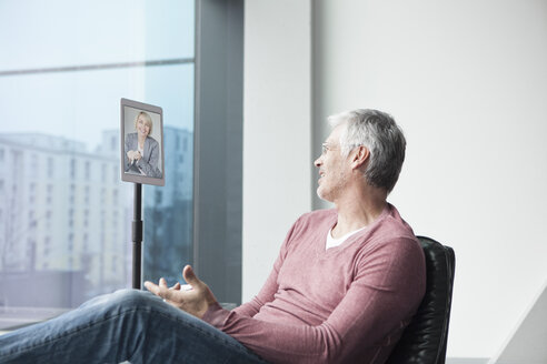 Man sitting in a leather chair using digital tablet for skyping - RBF002615