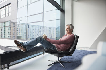 Man relaxing in a leather chair at home - RBF002621