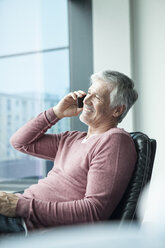 Man sitting in a leather chair telephoning with smartphone - RBF002624
