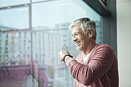 Smiling man with smartwatch looking through window - RBF002627