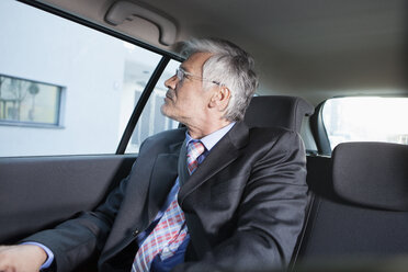 Businessman sitting in a car watching something outside - RBF002648