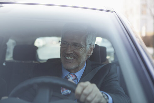 Portrait of smiling businessman in his car - RBF002651