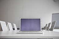 Opened laptop standing on conference table - RBF002654