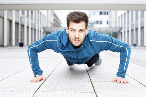Germany, Magdeburg, portrait of young man doing pushups - SEGF000312