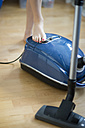 Woman's foot switching on vacuum cleaner - CHPF000137