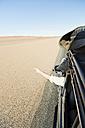 Namibia, Namib Desert, Namib Naukluft Park, Sossusvlei, man in a car pointing with his finger - CLPF000095
