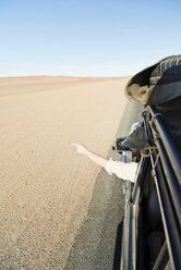 Namibia, Namib Desert, Namib Naukluft Park, Sossusvlei, man in a car pointing with his finger - CLPF000095