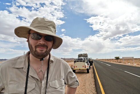 Namibia, Man with Safari hat and sunglasses with car at roadside in background - CLPF000105