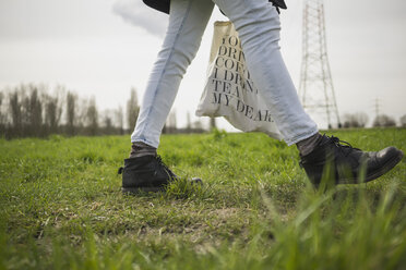 Germany, Zons, woman walking on a meadow - RIBF000012