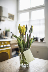 Adhesive note gluing at glass with tulips on a kitchen table - RIBF000021