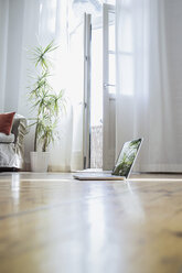Laptop standing on wooden floor of a living room - RIBF000024