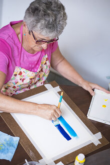 Senior woman painting an abstract picture - ABAF001650