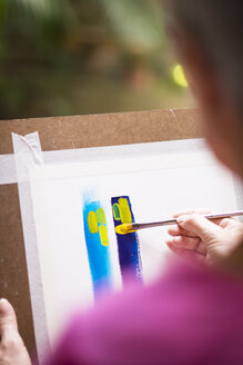 Woman painting an abstract picture - ABAF001654