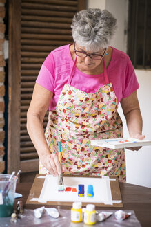 Senior woman painting an abstract picture - ABAF001656