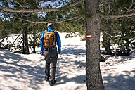 Spain, Catalonia, man with backpack hiking in the Pyrenees in winter - GEMF000209