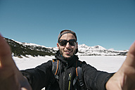 Spain, Catalonia, man taking a selfie in the mountains with frozen Lac des Bouillouses in the background - GEMF000211