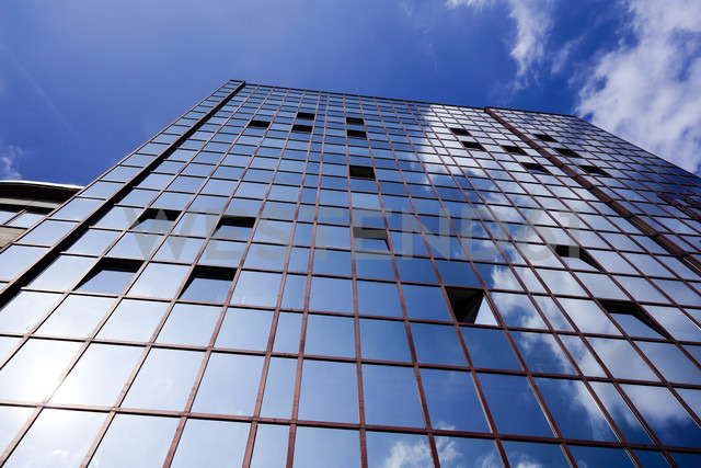 Germany, Dortmund, facade of an office building with reflection of clouds - HOHF001340