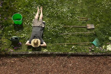 Man lying in grass relaxing from gardening - MIDF000353