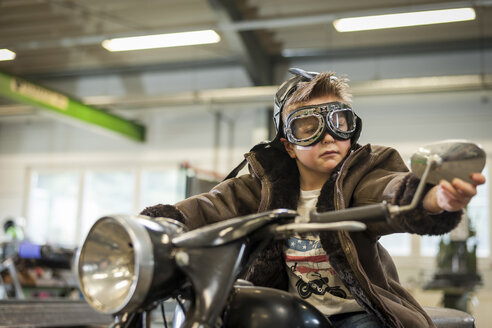Boy pretending to drive vintage moped - PAF001271