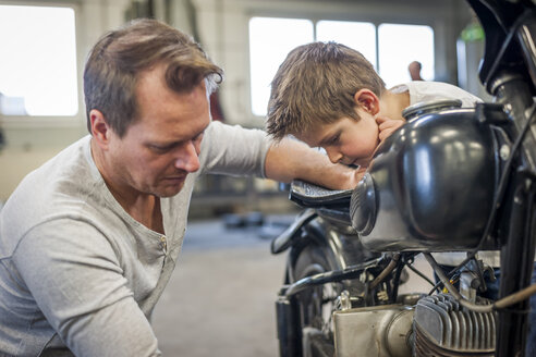 Father and son maintaining vintage moped - PAF001278