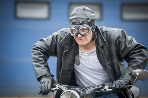 Man with leather jacket sitting on vintage moped - PAF001283