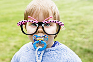 Portrait of baby girl with pacifier wearing fun butterfly glasses - GEMF000212