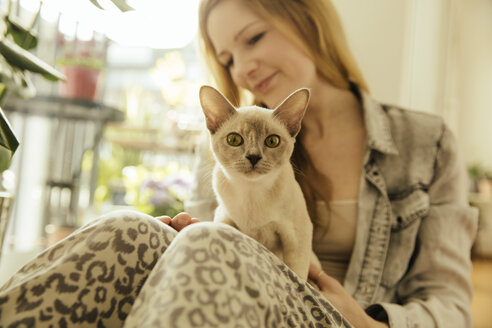 Woman with Burmese cat at home - MFF001562