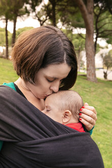 Mother kissing her sleeping son in baby sling - GEMF000217