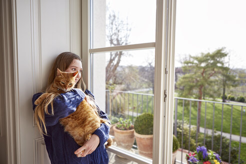 Female teenager with cat looking through window - DISF002029