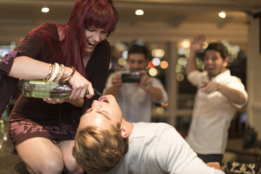Young woman befuddling a man with alcohol - ZEF005330
