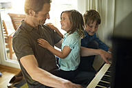 Father playing piano with daughter on his lap, son watching - MAO000054