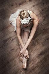 Female ballet dancer sitting on ground - DAWF000328