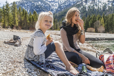 Austria, Tyrol, Lake Plansee, mother and daughter resting at lakeshore - TCF004620