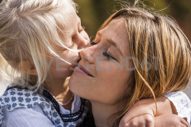 Girl hugging and kissing smiling mother - TCF004606 - Tom Chance/Westend61