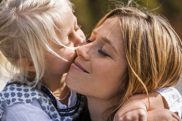 Girl hugging and kissing smiling mother - TCF004606