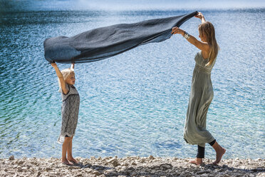 Austria, Tyrol, Lake Plansee, mother and daughter holding cloth at lakeshore - TCF004629
