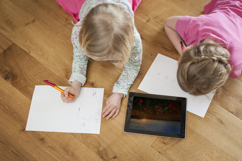 Two sisters with digital tablet and sheets of paper on floor - PAF001319