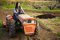 Farmer woman driving an old  tractor through a field - GEMF000220
