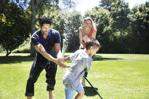Happy family splashing water with garden hose - TOYF000056
