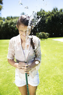 Young girl splashing water with garden hose - TOYF000062