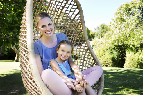Mother and daughter relaxing in hanging chair - TOYF000125