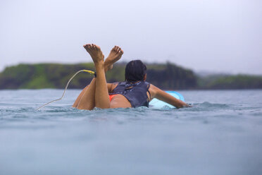 Indonesia, Lombok Island, woman relaxing on surfboard in the water - KNTF000015
