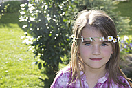 Portrait of little girl wearing floral wreath of daisys - YFF000409